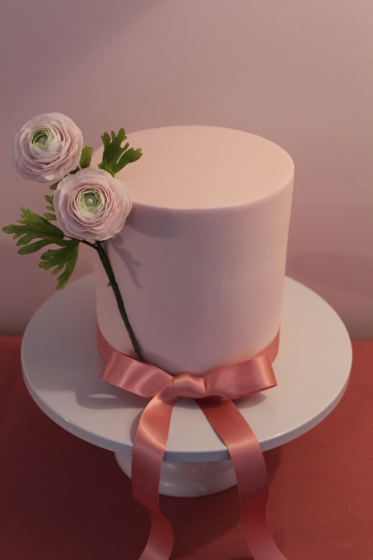 Sugar ranunculus on a rich chocolate cake with white chocolate ganache and fondant icing.